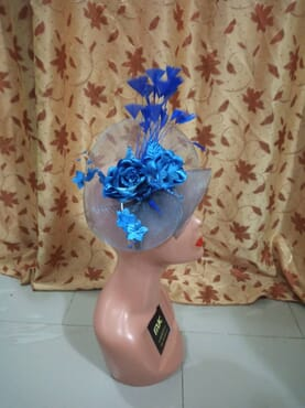 Nude fascinator designed with royal blue dazzling rose and features